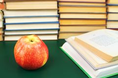 Apple on the green table and opened books. Red apple on the green table and opened books against a background pile of books royalty free stock photo