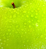 Apple in green with water drops. On its surface Royalty Free Stock Photo