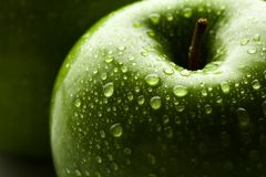 Apple in green with water drops on its surface Stock Images