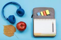 Apple, h?rlurar, torrt blad, ?ppen skrivbok p? p?se-blyertspenna fall med f?rgfiltpennor och mark?r p? bl? bakgrund arkivbilder