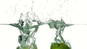 Apple halves plunging into water on white background stock footage