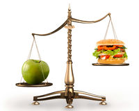 Apple and hamburger on scales conceptual hi-res. Big green ripe apple and junk food hamburger on scales isolated white background high resolution Royalty Free Stock Photography