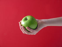 Apple in hand on red Stock Photo