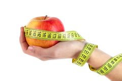 Apple in hand with a tape measure on white background stock image