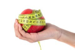Apple in hand with a tape measure on white background stock photography