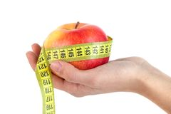 Apple in hand with a tape measure on white background royalty free stock image