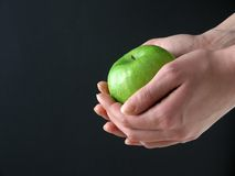 Apple in hands. Green Apple in hands on black background royalty free stock photo