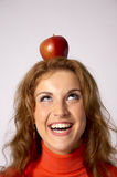 Apple on head. A young woman looking up at the apple she is balancing on her head Royalty Free Stock Images