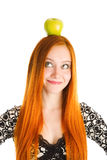 Apple on the head. Red haired girl with an apple on the head Stock Photography