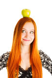 Apple on the head. Red haired girl with an apple on the head Stock Images