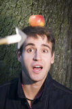 Apple on head with arrow. Young nervous man with the arrowed apple on the head Stock Photos