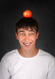 Apple on the Head. Happy Teenager with an Apple on the Head on the dark background Royalty Free Stock Image