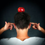 Apple on the Head. Rear View of the Man with an Apple on the Head on the Dark Background Stock Images