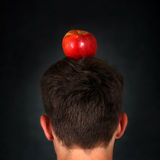 Apple on the Head. Rear View of the Man with an Apple on the Head on the Dark Background Royalty Free Stock Image