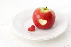 Apple with a heart shaped cut-out on a plate. Red apple with a heart shaped cut-out on a plate Royalty Free Stock Photos