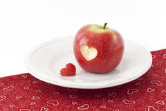 Apple with a heart shaped cut-out on a tablecloth. Red apple with a heart shaped cut-out on a tablecloth Stock Photo