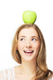 Apple on her head. Portrait of cheerful woman with apple on her head, over white Stock Photos
