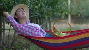 Apple-het gewas, de dromen van het landbouwersmeisje terwijl het ontspannen in hangmat en eet fruit van mand na binnen het opneme stock footage