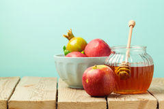 Apple and honey on wooden table over blue background Stock Images