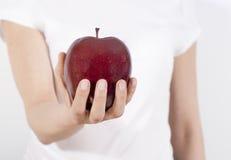 Apple i en hand Arkivbild