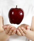 Apple i en hand Royaltyfria Foton