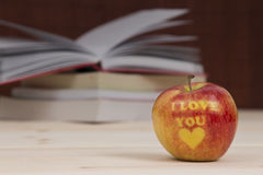 Apple with I love you inscription and books in the background Stock Photo