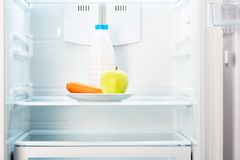 Apple i marchewka na bielu talerzu z butelką w chłodziarce Zdjęcia Royalty Free