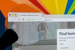 Apple iMac com o homepage de Airbnb na tela de monitor sob a lupa Airbnb é serviço de oferecimento do mercado em linha a alugar Foto de Stock