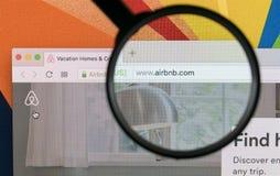 Apple iMac com o homepage de Airbnb na tela de monitor sob a lupa Airbnb é serviço de oferecimento do mercado em linha a alugar Fotografia de Stock