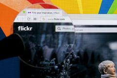 Apple iMac with Flickr homepage on monitor screen under magnifying glass. Flickr is the video hosting network website. Homepage Stock Photo