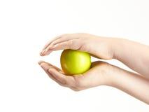 Apple imprensou entre as mãos dos childs Fotografia de Stock Royalty Free