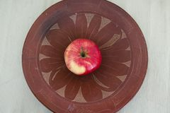 An apple inside a ceramic plate stock images