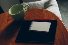 Apple iPad, φλιτζάνι του καφέ και σημειωματάριο στο ξύλινο γραφείο Στοκ Εικόνες