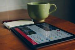 Apple iPad, φλιτζάνι του καφέ και σημειωματάριο στο ξύλινο γραφείο Στοκ Εικόνα