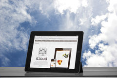 Apple iPad 2 in the clouds. Apple iPad 2 on a glass table, with the Safari browser opened on the official iCloud website and blue cloudy sky in background Stock Photos