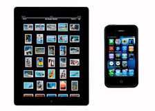 Apple iPad 2 - iphone4S - Isolated. An Apple iPad 2 showing the photo library and an iPhone4S showing the Apps display. (This iphone also has the outer rubber stock photography