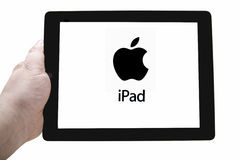 Apple ipad. A hand holding an Apple ipad with logo