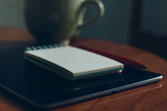 Apple iPad, cup of coffee and notebook on wooden desk Stock Images