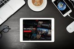 Apple iPad Gold with with Netflix  app on the screen. Kyiv, Ukraine - Fabruary 6, 2018: Apple iPhone 8 plus with Netflix app on the screen on black desk, top Royalty Free Stock Photo