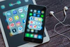 Apple iPad och iPhone med symboler av socialt massmedia Sociala massmediasymboler chart den genomskinliga sk?rmen f?r marknadsf?r arkivfoton