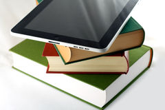 Apple ipad on a stack of books. This is an image that compares the iPad with books, highlighting its role as ebook reader Stock Photography