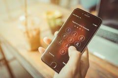Apple iPhone6 in één hand wordt gehouden die het zijn scherm met numpad voor het ingaan van het wachtwoord tonen dat stock afbeeldingen