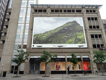 Apple Iphone 6 camera ad on the side of building with Loft store Stock Image