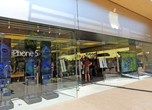 Apple iPhone Crowd. The front of a USA Apple Store showing an iPhone 5 sign and people lined up in queue.  The iPhone 5 was released in mid-September 2012, days Royalty Free Stock Photography