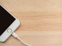 Apple iPhone6, das mit Blitz USB-Kabel auflädt Lizenzfreie Stockfotos