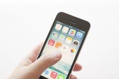 Apple iPhone i en kvinnlig hand Arkivfoto