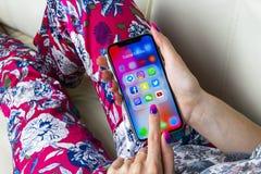 Apple iPhone X i kvinnahänder med symboler av social massmediafacebook, instagram, kvittrande, snapchatapplikation på skärmen Soc Royaltyfri Fotografi