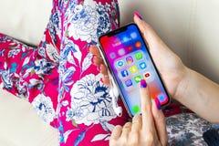 Apple iPhone X i kvinnahänder med symboler av social massmediafacebook, instagram, kvittrande, snapchatapplikation på skärmen Soc Arkivbilder