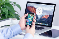 Apple iPhone with iOS 9 in male hands and Macbook Pro Retina