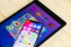 Apple iPhone X och iPad med symboler av social massmediafacebook, instagram, kvittrande, snapchatapplikation på skärmen Social ma Arkivbild